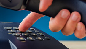 Closeup view of male hand holding telephone receiver dialing phone number on black landline telephone keypad.